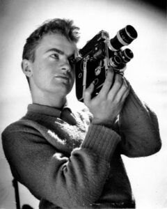 Stanley Fox posing with a Bolex movie camera. He is wearing a thick wool sweater with a collared shirt underneath. The Bolex camera is black and rectangular in shape and can be held comfortably with two hands. Fox is looking through the lens as though he is filming something.