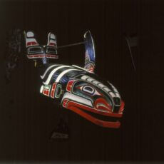 Carved wooden whale headdress painted black, red, green and white. The mouth, fins and tail of the whale are movable.