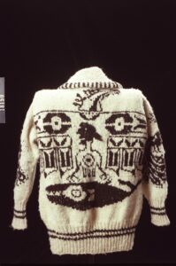 A photograph of the back of a white knitted sweater with dark brown designs depicting a thunderbird and whale.