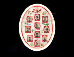 Ten black and white photographs of men and women are presented in an oval frame and decorated with needlepoint flowers.
