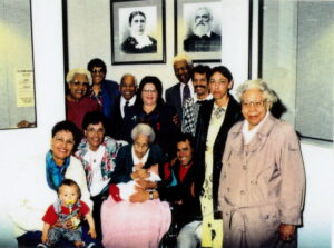 A family photograph including several generations. Older people sit with babies on their laps.