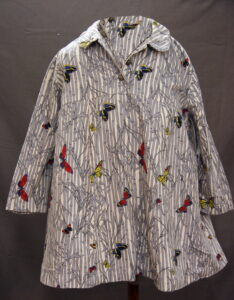 A maternity jacket with a pattern of colourful butterflies flying through grey-and-white bamboo.