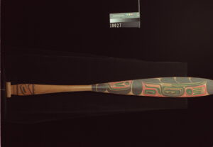 A photograph of a long-bladed canoe paddle with colourful Heiltsuk designs on its blade.