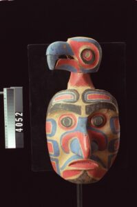 Carved wooden mask of human face with small bird head attachment on top. Mask is painted red and black.