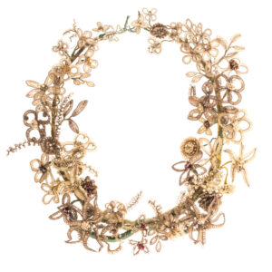 Garland made from woven human hair around wire, wrapped with green thread and is decorated with pretend pearls and metal beads.