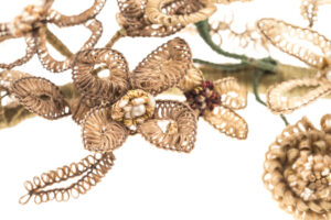 Close-up of a garland fashioned from human hair woven around wire. The wire is also wrapped with green thread and is decorated with faux pearls and metal beads.