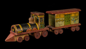 A photograph of a wooden toy train with a locomotive and a stock car.