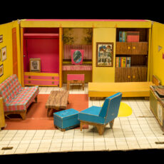Photograph of the inside of a house for Barbie dolls from the 1960s. It has a couch, chair, coffee table, television, bookshelves, windows and pictures on the wall, all in bright colours.