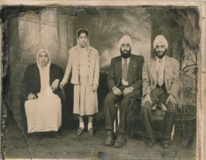 A black and white studio portrait of a South Asian family. An older woman in a long white garment with a dark coat sits at the left. Next to her stands a young woman in a skirt and jacket. Two men in suits and turbans sit at the right.