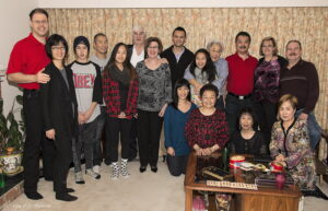 A Christmas holiday photograph of thirteen members of the Loy Sing Guen family in 2013, all casually dressed and smiling broadly. In the foreground is a table with a box of chocolates and other holiday treats on it.