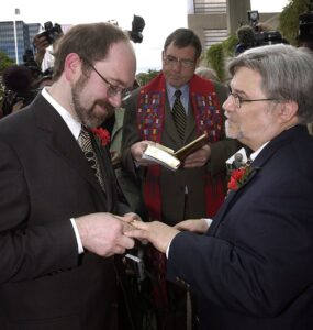 Two men exchanging wedding rings and vows. A United Church minister stands between them holding a book.