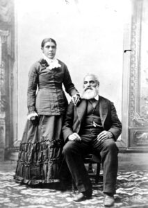 A black and white studio portrait of woman standing and her husband seated. They are wearing formal clothing.
