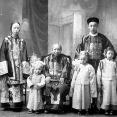 A studio portrait of a family in traditional Chinese-style clothing. In the middle sits an older woman, with three young children around her. Behind them stand a young woman and a young man.