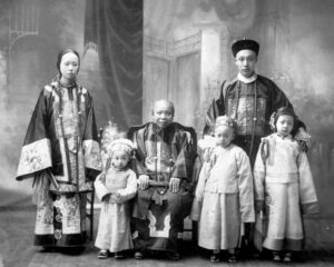 A studio portrait of Lee Mong Kow's family in traditional clothing. In the middle sits an older woman, with three young children around her. Behind them stand a young woman and a young man.