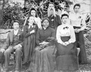A black and white photograph of a family sitting outside. In the centre sits an older woman in a dark dress. Behind her stands an older man with a bushy beard. Around them are five young people, including teenage boy with a dog at his side, two young girls and two young women.