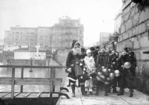 A black and white photograph showing Santa Claus standing on Victoria's Inner Harbour causeway with a group of young boys dressed as clowns standing next to him.
