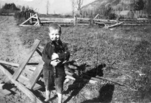 A black and white photograph showing a little boy standing barefoot in a field holding a black kitten.