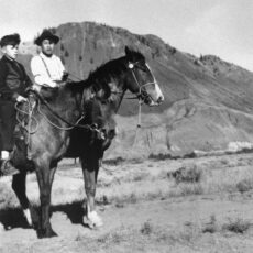 A black and white photograph of two young boys seated on horses in the middle of a desert valley with a big mountain behind them.