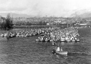 A black and white photograph showing many fishing boats tied up at docks in the water.