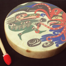 First Nations drum made of painted hide, wood, antler, cloth and string.