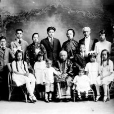 A studio portrait of a Chinese Canadian family. Eight men and women stand in the back, and in front seven boys and girls surround an elderly woman, seated, in a traditional silk dress. The men wear suits and ties. One of the women wears a European-style dress while the others wear Chinese-style silk jackets. All of the children wear European clothes.