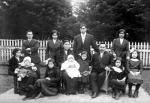 A black and white photograph that shows a large First Nations family, formally dressed, outside in a garden with their dog.
