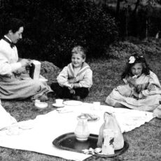 A black and white photograph of four children—three girls and a boy—and their aunt sitting on the grass having a picnic.