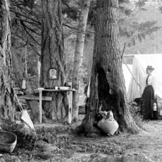 Black and white photograph of woman wearing a long black skirt standing in front of a tent.