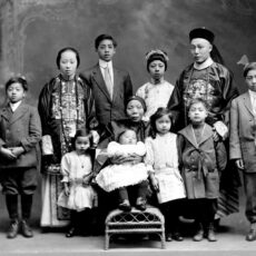 A studio portrait of a Chinese Canadian family in formal clothing. The parents wear traditional Chinese-style silk garments. The children wear European-style clothes.