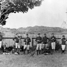 A black and white photograph of 12 young male lacrosse players dressed in striped shirts and white short pants with socks pulled up to their knees. They are standing and sitting by a fence under a large tree.