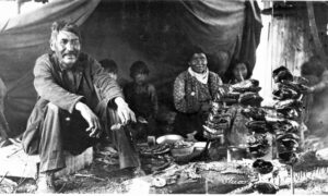 A black and white photograph showing a First Nations family sitting in a tent smoking salmon heads on sticks over a small fire.