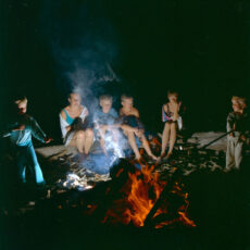 A colour photograph of six kids sitting on logs around a campfire.