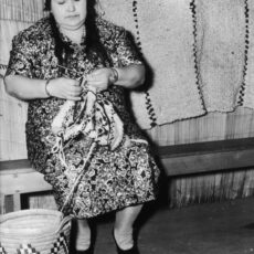 A black and white photograph of a seated woman knitting. A woven basket and knitted blanket are also visible in the picture.