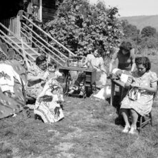 A black and white photograph of four First Nations women and girls sitting outside knitting traditional Cowichan sweaters. One of the knitters holds a toddler in her lap. A completed sweater with an eagle on it is on display.