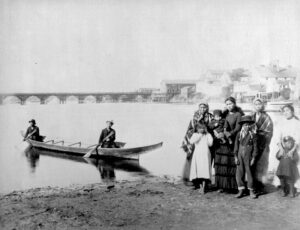 A First Nations family. Four women and four children stand on the muddy shore, while two men sit in a wooden canoe in the harbor. A bridge and some wooden buildings are in the background.