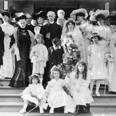 A black and white photograph of a 1905 wedding with the bride and groom in the middle of large group of friends and family.