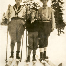 A black and white photograph showing a 10 year old girl standing in the snow between her mom and dad. All three are wearing skis.