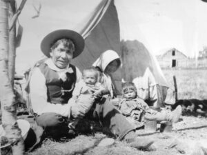 A black and white photograph of a First Nations man seated on the ground holding a baby. A woman sits next to him with a toddler on her lap.