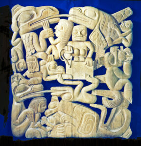 A pale cedar carving of intertwined Haida figures, including a fisherman and his wife who are surrounded by beings and creatures.