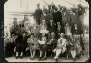 Image of people on a ship's deck in 1931. Front row are women sitting down. Middle row are women standing. Back row are men standing in suites. Person in front row has life preserver around her head.