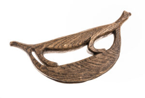 A carved, wooden mat creaser made to be held by a human hand.