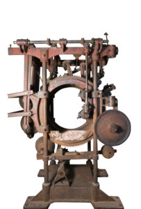 A large iron structure consisting of a series of wheels, gears and levers. The large centre wheel is perforated.