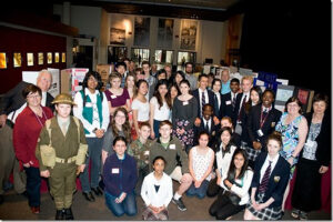 A posed photograph of about 35 Heritage Fair students with adults. Heritage Fair projects are in the background.