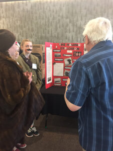 An adult judge at a Heritage Fair talking with three students in front of their project. The students are dressed in costumes.