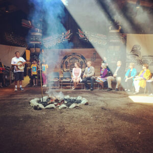 Image of a First Nations ceremony inside a big house. There are two totem poles in the background, a man stands with a drum leading the ceremony and six guests are seated near a lit and smoking fire.