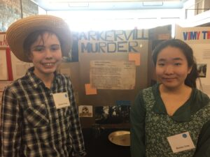 Two students posing in front of a school project about Barkerville, BC.