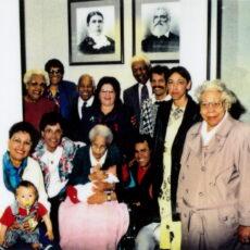 Une photo de famille réunissant plusieurs générations. Les aînés sont assis et tiennent des bébés sur leurs genoux.