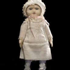 Une poupée de chiffon portant une robe et un bonnet blancs.