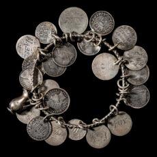 Un bracelet d'amitié ancien en argent, dont les breloques sont des pièces de monnaie, où des prénoms féminins tels qu'«Amy», «Mabel» et «Edith» ont été gravés.
