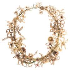 Couronne de cheveux humains tissés autour d'un fil de fer recouvert de ruban vert et décoré de fausses perles et de billes de métal.